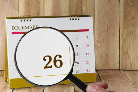 scheduling system: Magnifying glass in hand on calendar you can look Twenty-six date of month,Focus number Twenty-six in December,Concept in business and meetings.