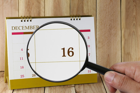 scheduling system: Magnifying glass in hand on calendar you can look Sixteenth date of month,Focus number sixteen in December,Concept in business and meetings. Stock Photo