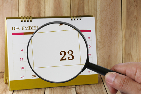 scheduling system: Magnifying glass in hand on calendar you can look Twenty-three date of month,Focus number Twenty-three in December,Concept in business and meetings.