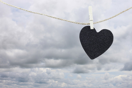 heartbreak: Black Heart paper hanging on a brown hemp rope on rain clouds background,Concepts about unrequited love and heartbreak.
