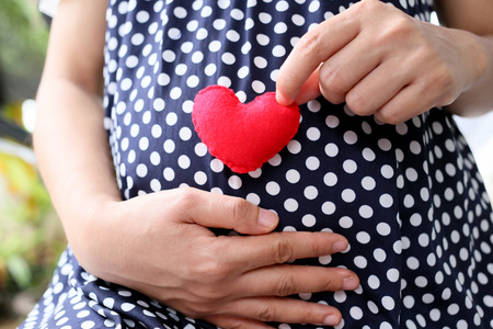 azul marino: Pregnant women wear navy blue maternity clothes and a red heart symbol placed on belly.