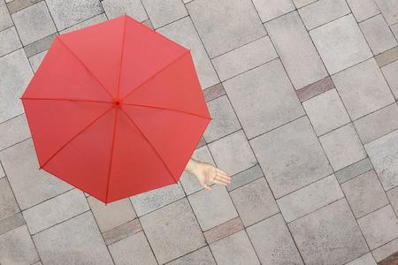piso piedra: Paraguas rojo y una mano del hombre que está en el piso de piedra y la mano que sobresale fuera del radio para determinar si llueve o no, el concepto de riesgos en los negocios.