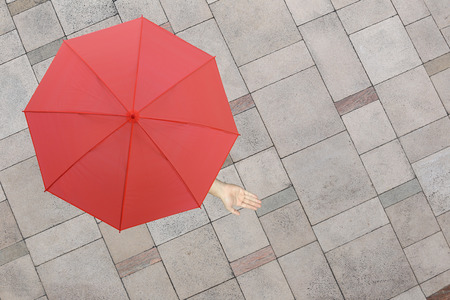 stone floor: Red umbrella and a hand of man standing on stone floor and hand protruding outside the radius to determine whether it rains or not,concept of risks in business.