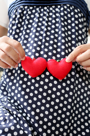navy blue: Pregnant women wear navy blue maternity clothes and a red heart symbol placed on belly.