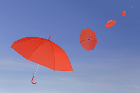 blown: Red umbrella blown by the wind in concept for management business idea on blue sky background.