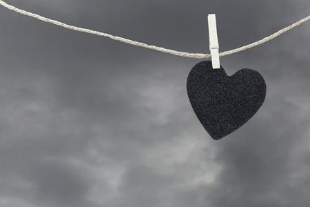 ブラック ハート紙雨の雲の背景、片思いや失恋についての概念に茶色の麻縄に掛かっています。 写真素材