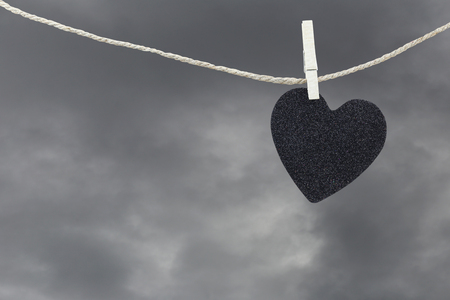 Black Heart paper hanging on a brown hemp rope on rain clouds background,Concepts about unrequited love and heartbreak.