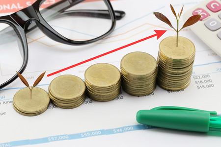 silver bars: silver coin stack and arrow line and have treetop in business growth concept on paper of report assessed income. Stock Photo