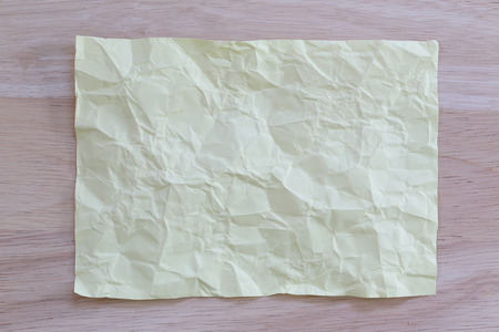 Yellow notepad paper crumpled of empty and copy space on wooden background,You can input the message text in picture. Stock Photo