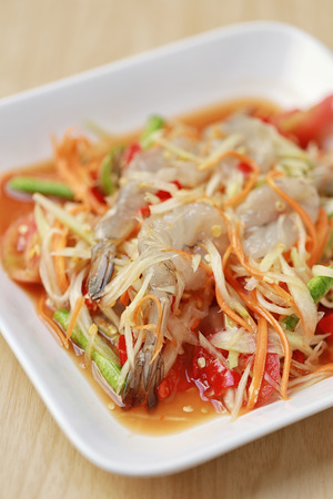 SOM TUM,Thai foods or papaya salad with fresh shrimp in spicy taste and is popular in thailand on wooden table background.