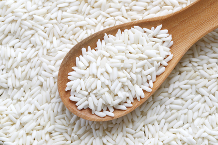 Organic white rice in wooden spoon, glutinous rice or sticky rice for design nature foods Concept.