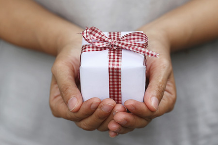 White Gift box on women hands in concept Christmas Day and New Year or give in a special time.
