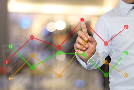 Finger of businessman touch to the peak of business graph on abstract blur background,concept to success and profitability.