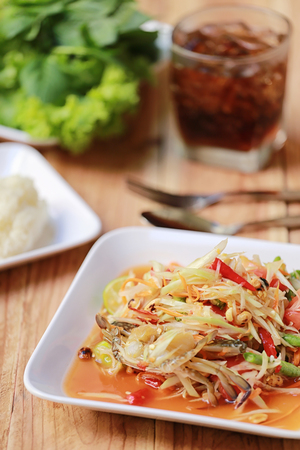SOM TUM,Thai foods or papaya salad in spicy taste and is popular in thailand on wooden table background.
