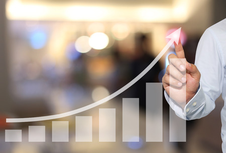 ビジネスマンの成功と収益性に来る概念財務記号抽象的なぼかしの背景にピークのビジネス グラフにタッチへ。