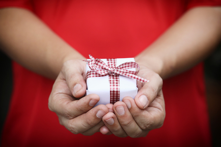 obtaining: White Gift box on women hands in concept Christmas Day and New Year or give in a special time.