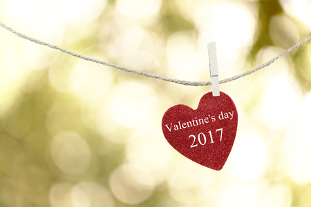 Red Heart hung on hemp rope and have text Happy Valentines Day 2017 on abstract color of boken background.