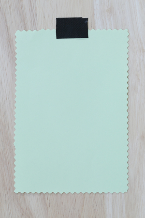 Green notepad paper of empty and copy space on wooden background,You can input the message text in picture.