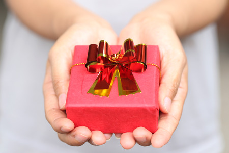 obtaining: Red Gift box on women hands in concept Christmas Day and New Year or give in a special time.
