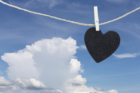 hung: Black Heart hung on hemp rope on blue sky background and have copy space to manage the text you want. Stock Photo