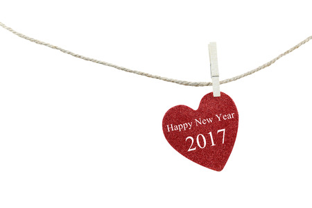 objects with clipping paths: Red heart with text of Happy new year 2017 hanging on hemp rope isolated on white background and have clipping paths to easy deployment. Stock Photo