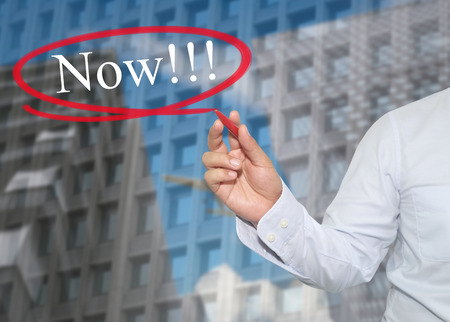 promote: Hand of young businessman write the word Now on skyscrapers background,concept of Apply to promote your business or work presentations.