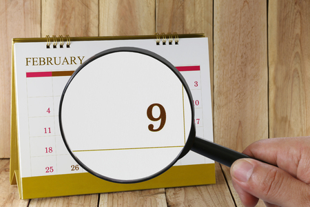 numero nueve: Magnifying glass in hand on calendar you can look ninth day of month,Focus number nine in February,Concept in business and meetings. Foto de archivo