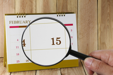 number 15: Magnifying glass in hand on calendar you can look Fifteenth day of month,Focus number fifteen in February,Concept in business and meetings. Stock Photo