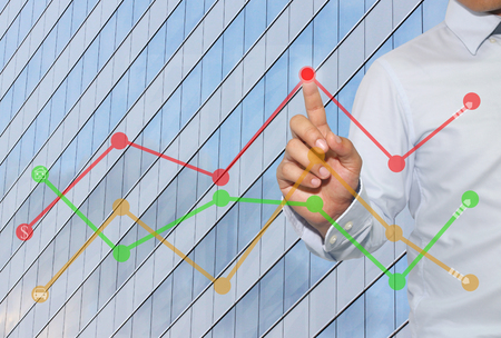 Finger of businessman touch to the peak of business graph on Skyscraper background,concept to success and profitability.