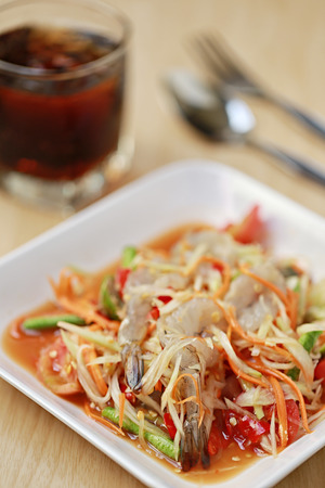 slatternly: SOM TUM,Thai foods or papaya salad with fresh shrimp in spicy taste and is popular in thailand on wooden table background.
