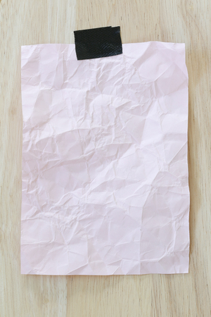 Pink notepad paper crumpled of empty and copy space on wooden background,You can input the message text in picture. Stock Photo