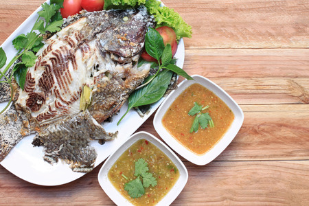 Tilapia fish grilled with Salt in white dish and have Spicy Sauce,Thai foods style placed on wooden table.