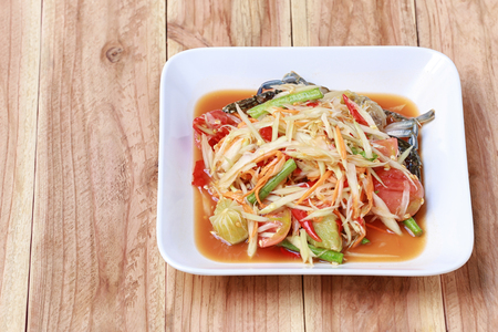 SOM TUM,Thai foods or papaya salad in spicy taste and is popular in Thailand on wooden table background. Stock Photo