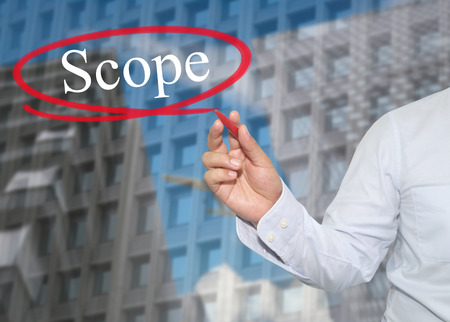 promote: Hand of young businessman write the word Scope on skyscrapers background,concept of Apply to promote your business or work presentations. Stock Photo