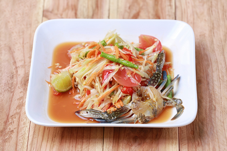 slatternly: SOM TUM,Thai foods or papaya salad in spicy taste and is popular in Thailand on wooden table background. Stock Photo