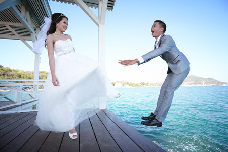 bride kicking a Bridegroom,Pre Wedding photography thai couples at Koh Si Chang Island concept in memory of love. Stock Photo