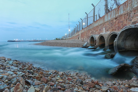 Drainage pipe with water flowing into the sea in the evening. Stock Photo