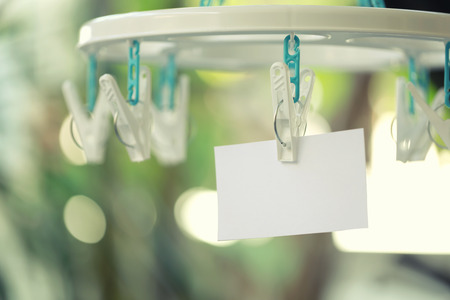 notepaper: white paper notes hanging in a clothesline on green bokeh background.