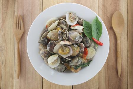 ridged: sea clams or RIDGED VENUS CLAM of Stir sauce in white dish on wood background.