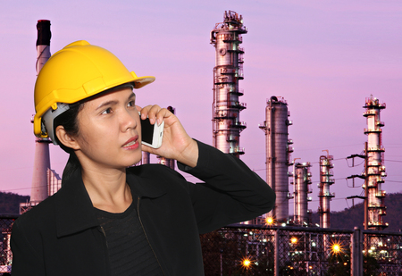 Business women are talking on the phone and Oil refineries background in concept of negotiation and presentation.
