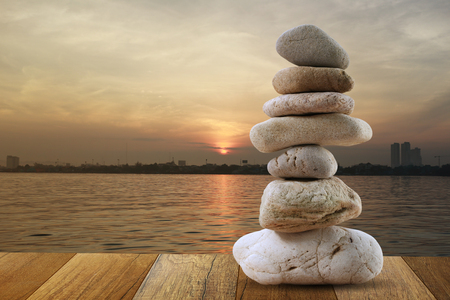 Balanced stone of pyramid for meditation on brown wood floor and coast at Sunrise. Stok Fotoğraf