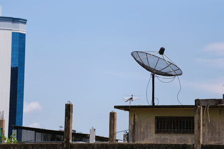 Black Satellite dish on Roof house for Concepts of Connectivity and Communication Technology. Stock Photo