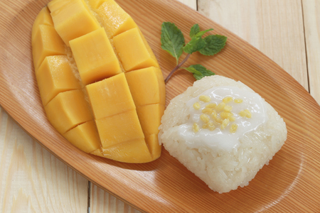 Traditional Thai dessert of mango with sticky rice mix coconut milk in wooden dish on foods table.