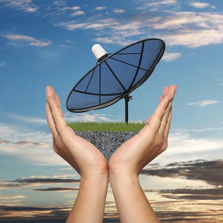 satelite: Black Satellite dish in hand of businessman on sunset background,Concept of data communication.