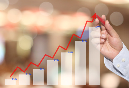 hand of Businessman point to line graph business in top,concept of business investment and profits and assessed.