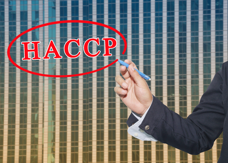 hand of a business man use a pen write text system HACCP on glass wall of tall building background.