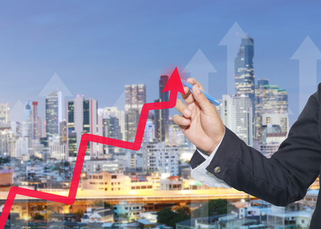 hand of businessman using blue pen pointing to top arrow graph on background of tall buildings in twilight time,concept of investment and profits.
