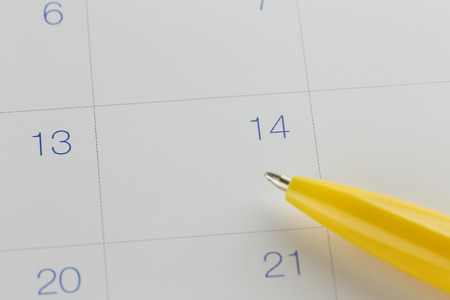 yellow pen points to the number 14 on calendar background in concept of appointment schedules and important dates.