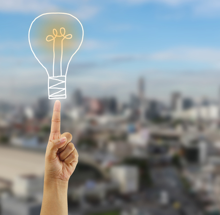 fingers of businessman point to the light bulb symbol in concept of starting a business and present in your work. Stock Photo