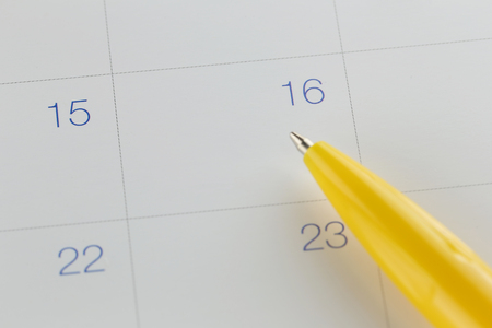 yellow pen points to the number 16 on calendar background in concept of appointment schedules and important dates.
